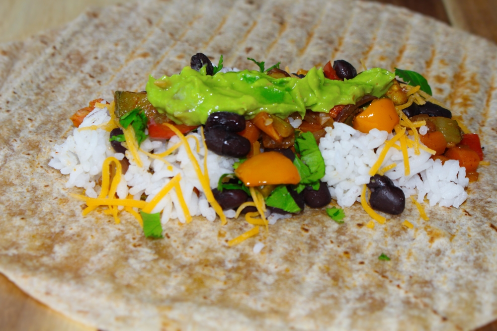 Layering Burrito with Black beans, white rice, Guacamole,Veggies and cheese